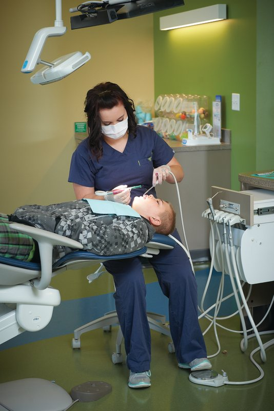 A dental hygienist working on a child lying on a dental chair at Tiny Teeth Pediatric Dentistry.