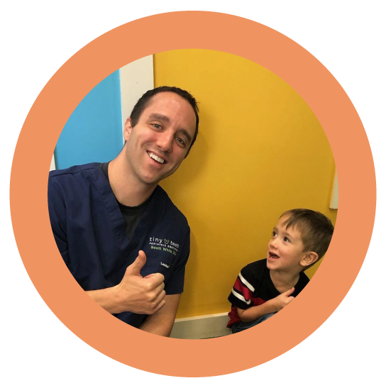 Dr. Scott smiling and giving thumbs up with kid at Tiny Teeth Pediatric Dentistry