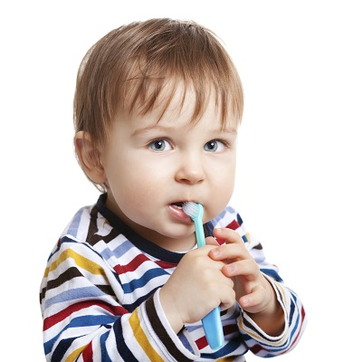 Baby in striped shirt holding a toothbrush in mouth